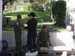 A haredi man wraps Tefillin on a soldier in Hebron in 2005 (Frantzman)