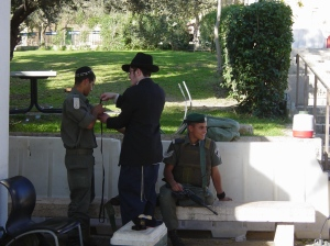 A haredi man wraps Tefillin on a soldier in Hebron in 2005 (Frantzman)