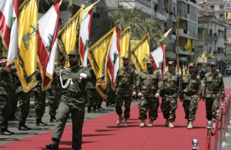 Hezbollah fighters parade before leaving for Syria