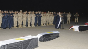 Then general Abdel Fattah al-Sisi prays  with soldiers next to the bodies of Egyptian conscripts murdered in Sinai in January 2014