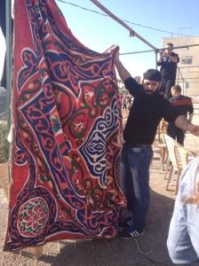 Men hanging a curtain at the mourner's tent (Seth J. Frantzman)
