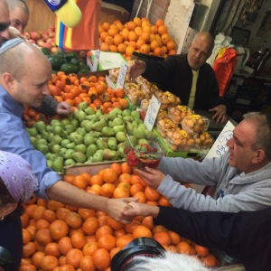 "Naftali Bennet buys fruit during an election stop in Jerusalem. Voters of the right are called ""racist""; while the left adopts his ""no apologies"" rhetoric. (Seth J. Frantzman)"
