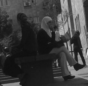 An Arab and Jewish woman sit on a bench in Jerusalem; some people see the city as