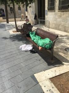 A man sleeps on a bench in Jerusalem (Seth J. Frantzman)