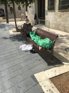 A man sleeps on a bench in Jerusalem (Seth J. Frantzman)